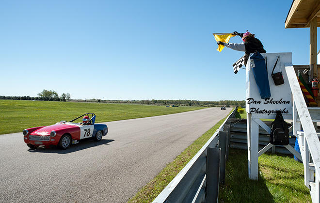 Vintage Sports Car With Checkered Flag And Caution Flag  At Gingerman Raceway In South Haven, Michigan.