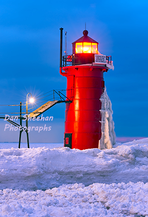 The South Haven, Michigan Lighthouse With The Beacon Brightly Lit And A Frozen Solid Lake Michigan Surrounding It. This Famous Great Lakes Lighthouse Is An Important Aid To Navigation. Dan Sheehan Photographs